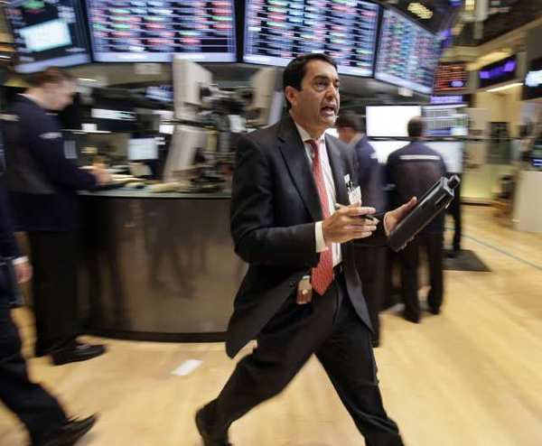 As stocks opened on a downward trend Friday, trader Mark Muller hustles across the floor of the New York Stock Exchange.