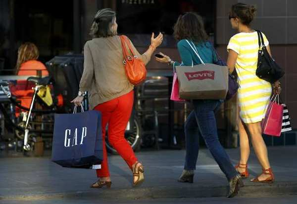 Pedestrians carry shopping bags at the Third Street Promenade in Santa Monica. Consumer spending is up, but personal incomes are down, according to a government report Friday.