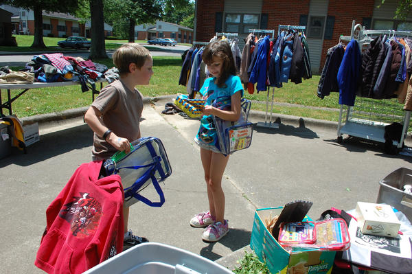 Ezra Lynn, left, checks out the latest find of friend Leah Marshall at Thursday's free yard sale in Junction City sponsored by the Boyle County Family Resource Center. Ezra and Leah, both 7, are neighbors who made several visits to the yard sale.
