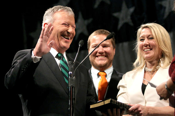 Orlando mayor Buddy Dyer laughs, with wife Karen and son Trey, after flubbing his lines while reciting the Oath of Office, during the swearing-in ceremony, Friday, June 1, 2012, at Bob Carr Auditorium in Orlando. Dyer and four city commissioners were sworn-in.