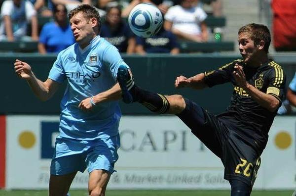 Michael Stephens, right, competes for the ball with Edin Dzeko of Manchester City during a July 2011 Galaxy game.