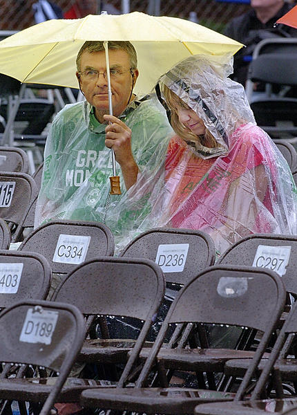 Skip Prior and Karen Kneisley of Bradenton, Fla. wait out the rain for the next band to come on at Blues Fest on Friday.