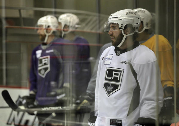 Kings center Mike Richards, right, and his teammates are distorted by the plexiglass surrounding the rink during a team practice session on Friday.