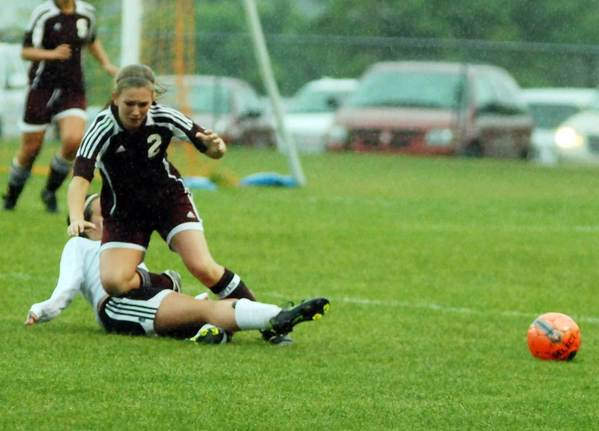 Charlevoix's Kelly Greyerbiehl (2) falls after a successful slide tackle by Robin Trierweiler of Elk Rapids Friday during a Division IV district championship game at Ottawa Stadium in Harbor Springs. The Elks won, 1-0.