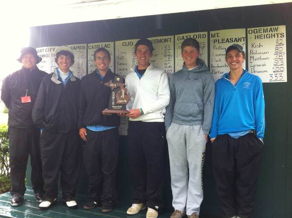 Coach Chad Loe (left) and members of his Petoskey High School golf team pose with the trophy Thursday after winning a Division II district title at Cadillac Country Club.