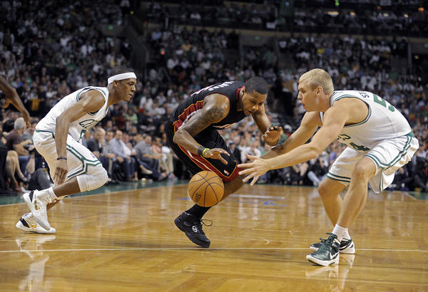 Miami Heat guard Mario Chalmers dribble in between the defense of Boston Celtics Rajon Rondo and Greg Stiemsma during the first half of Game 3 of their Round 3 playoff series,