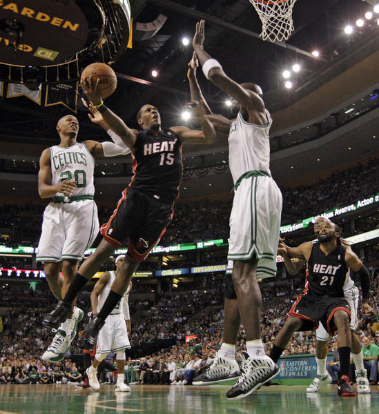 The Miami Heat's Mario Chalmers (15) goes up against the Boston Celtics' Ray Allen (20) and Kevin Garnett in the first quarter in Game 3 of the Eastern Conference Finals