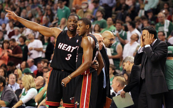 Dwyane Wade (3) and Mario Chalmers confer on the court as the Miami Heat trail in the first half, while head coach Eric Spoelstra reacts at far right, against the Boston Celtics in Game 3