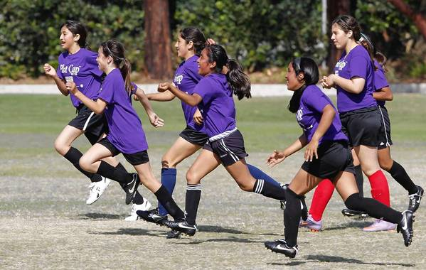 Members of the Whittier girls' 5-6 bronze division team run off the field in celebration after beating Waldorf at the Daily Pilot Cup.