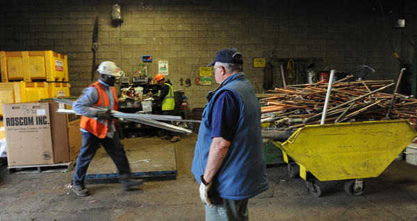 (left)Thadeus Howell, of Allentown weighs and separates scrap metal. (right) Ed Komnath brings a bag of soda cans, an aluminum door frame and old Honda car parts that his son-in-law couldnÕt sell at a yard sale to E. Schneider & Sons Inc. ÒIt adds up,Ó said Komnath, of Macungie, he said: ÒI can take my grandson to Burger King.Ó Komnath, walked away with $13.40 in cash. By selling used metals, consumers can pick up extra dollars and ensure their recyclable items stay out of a landfill. Demand for steel and other metals means scrappers are looking to get the most for their money. People can turn unwanted metal items from cat food cans to car parts and pipes into extra cash. Photo taken at E. Schneider & Sons Inc.