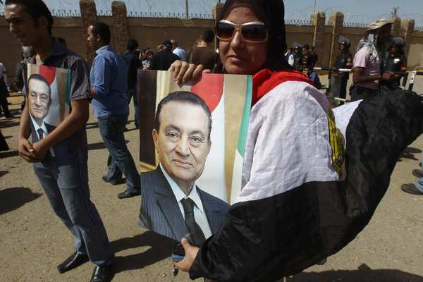 Supporters of Egypt's ousted president Hosni Mubarak (portraits) wait for the verdict outside the courthouse in Cairo on June 2, 2012.