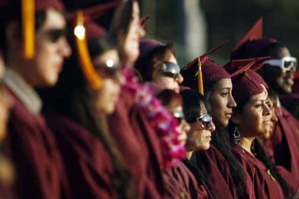 Glendale Community College's Rosenda Colmenares, from third right, and other graduates line up as they listen to the Chambers Singers Men perform during GCC's graduation ceremony in Glendale.