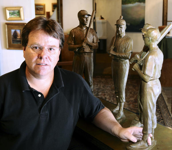 Toby Mendez stands in front of a sculpture of four Boston Red Sox players. He has been commissioned to sculpt six statues for Baltimore Orioles.
