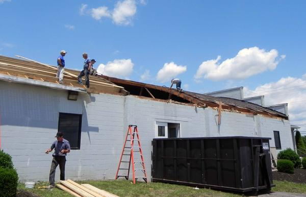 Crews repair the storm-damaged roof of Mercersburg Printing at 9964 Buchanan Trail West, Mercersburg, Pa. The business suffered damage to a 3,000-square-foot section of its roof, as well as water damage to the interior of the building from Friday's thunderstorms.