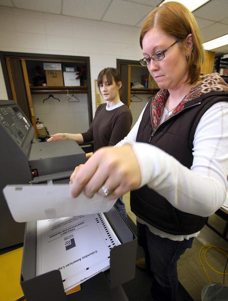 Lisa Wienk, right, collects a bad ballot as she and fellow Brown County deputy auditor Julia Grenz run a test of the ballot scanner Friday in preparation for Tuesday's election. The test includes ballots that have been deliberately over-voted to make sure the machine detects the error. American News Photo by John Davis