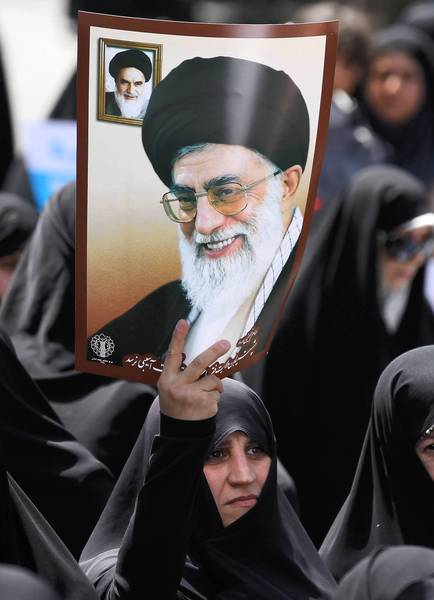 A woman holds up a portrait of Iran's leader, Ayatollah Ali Khamenei, right, and his predecessor the late Ayatollah Ruhollah Khomieni during a protest in Tehran last month.