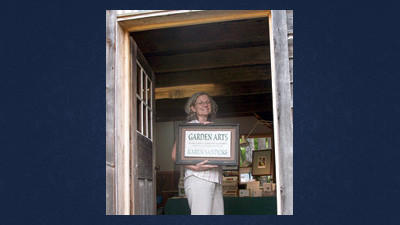 Pennsylvania artist Karen Sandorf displays her sign in the doorway of Spruce Forest's Hochstetler House each fall. Hochstetler House is one of three historic buildings occupied monthly by visiting artists during the summer and fall at the Artisan Village in Grantsville.