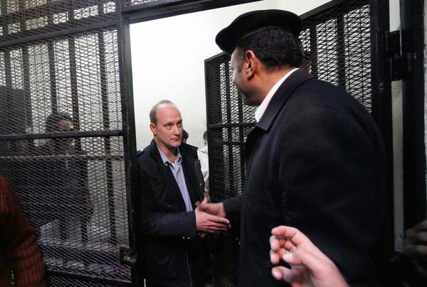 American Robert Becker of the National Democratic Institute, left, leaves the defendants cage after a hearing in the trial of employees of nongovernmental organizations in Cairo in March.