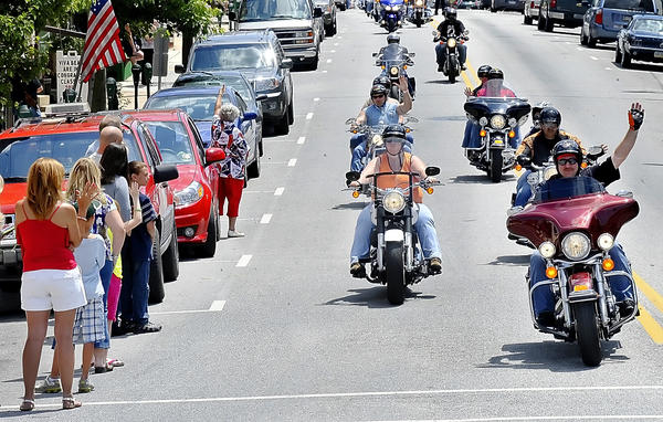 People line the streets of downtown Greencastle, Pa., Sunday to wave to motorcyclists taking part in the God Bless America ride.