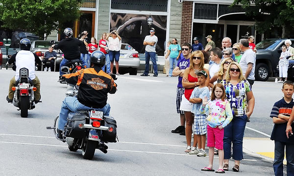 People line the streets of downtown Greencastle, Pa., to wave to motorcyclists participating in the God Bless America ride to benefit the Veterans Affairs center in Martinsburg, W.Va.