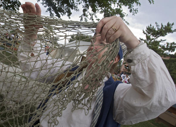 Nancy Robbins of the Baltimore-based Vigilant Crew hangs up a fish net to dry at the Blackbeard Pirate Festival in Hampton on Saturday.