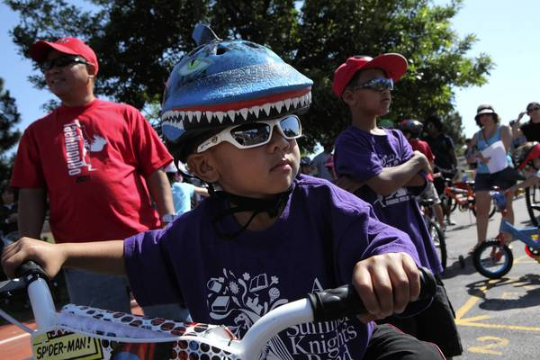 On Sunday in Skokie, a few hundred people, including Matthew Deniga, 3, and his brother JM, 8, take part in a bike safety procession for Carter Vo, 8, who was killed by a car while riding his bike. Carter and JM were classmates.