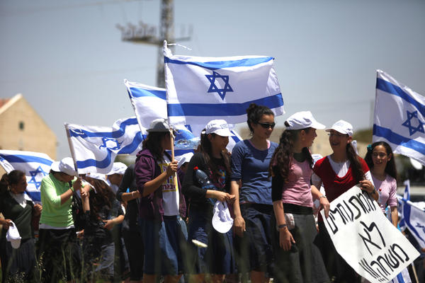 Israeli settlers wave their national flag as they participate in a march from the Ulpana outpost, in the West Bank settlement of Beit El, to the High Court of Justice in Jerusalem.