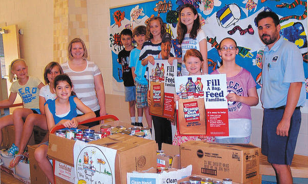 Rockland Woods Elementary School students who participated in the food drive, are, front row, from left, Molly McCook, Ashley Kopp and Ally Frushour. Back row, Garrett Woods, Iggy Chalker, Devin Riss, Ava Willett, Kerri Byrum and Carsyn Shipway. The letter carrier, at far right, is Bryan Chaney. The teacher, at left, is Katie Rubeck.