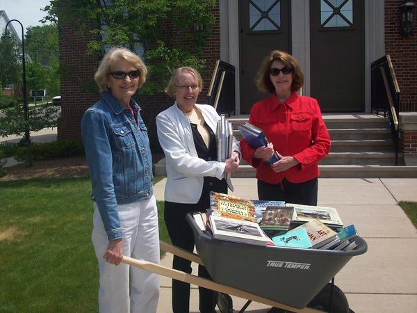 "Friends of the Petoskey District Library (from left) Jane Damschroder, Joyce Hutto-Nolan and Suzanne LaBeau are busy collecting book donations for the Friends' ""Drive By, Drop Off"" used book drive, scheduled for Saturday, June 9, in front of the library. Meyer Ace Hardware has loaned a wheelbarrow for the occasion."