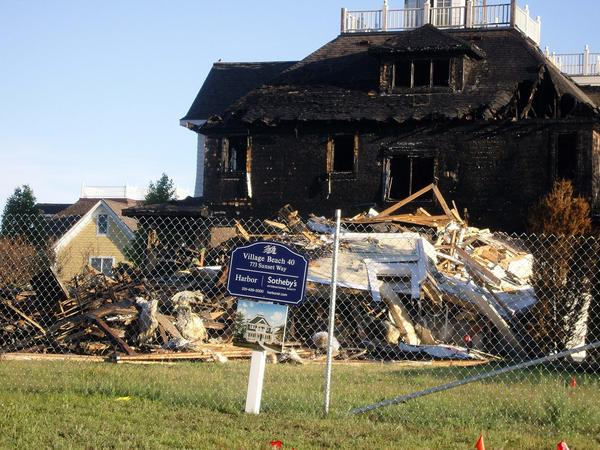 A pile of debris remains where a house once stood in Bay Harbor. The house was destroyed by fire last month. A neighboring house was badly damaged by the blaze.