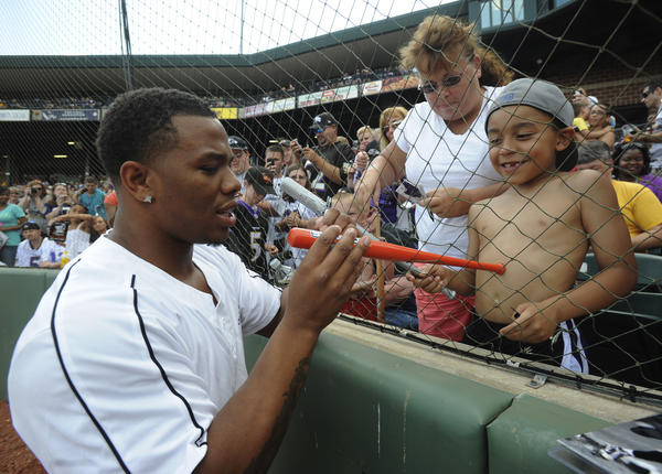 Ravens star Ray Rice signs a tiny bat for Tony Ennis, 6, as his grandmother Mary Acton of Pasadena looks on. Rice was among the athletes on hand for the Lardarius Webb Charity Softball Game held Sunday at Ripken Stadium in Aberdeen.