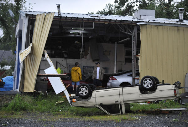 Employees of All Pro Auto Body survey the damage to their building after a powerful storm ripped through Fallston in Harford County.