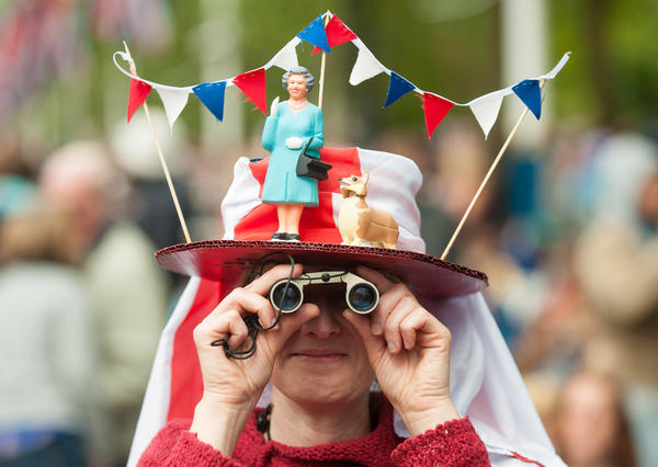 A woman in a fancy dress hat featuring Queen Elizabeth II and a corgi waits for the start of the Diamond Jubilee, Buckingham Palace Concert May 04, 2012 in London, England.