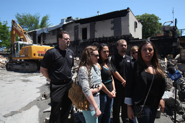 Johanna Parra, Marketing Director of Roy's Furniture, right, along with employees of the business announce Monday that they will be operating out of their warehouse for now and rebuilding on the same site in the Lincoln Park neighborhood.