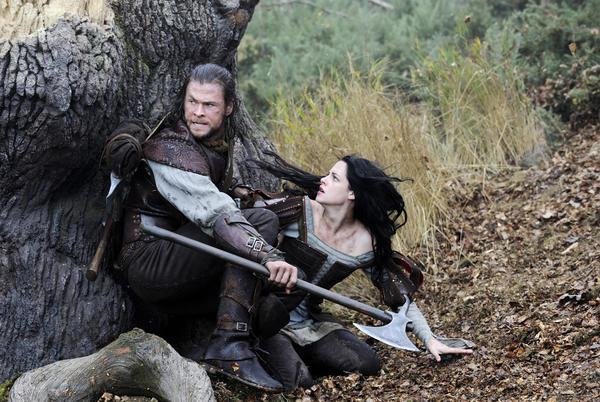 "This film image released by Universal Pictures shows Chris Hemsworth, left, and Kristen Stewart in a scene from ""Snow White and the Huntsman."""