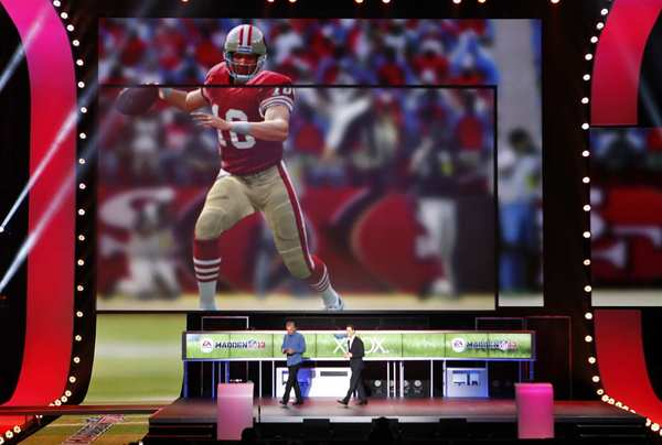 "Andrew Wilson of EA Sports, right, and quarterback Joe Montana, left, demonstrate play calling on Electronic Arts' ""Madden 13"" at E3."