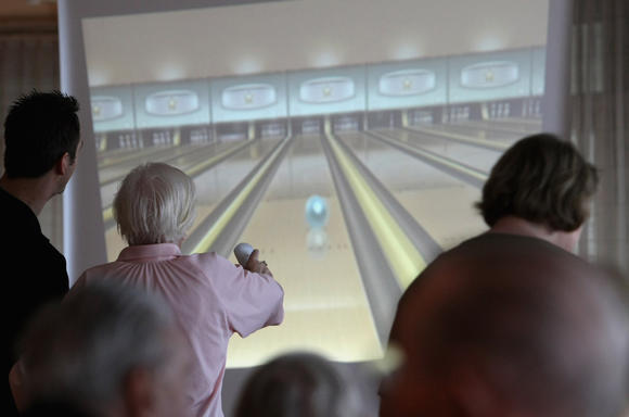 Participant plays Nintendo Wii bowling at a senior citizen home