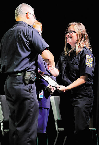 Smithsburg High School senior Samantha Palmer, right, shakes hands with instructor Dan Garnand as she picks up her Washington County Fire & Rescue Academy graduation certificate Monday night at South Hagerstown High School.