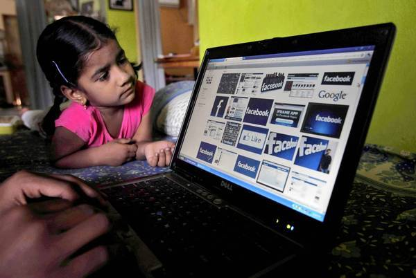 Even though Facebook says it shuts down every underage account it finds and has tried to beef up its age verification systems, it privately concedes that there are millions of underage kids on Facebook. Above, a child looks at a laptop displaying Facebook logos in Hyderabad, India.