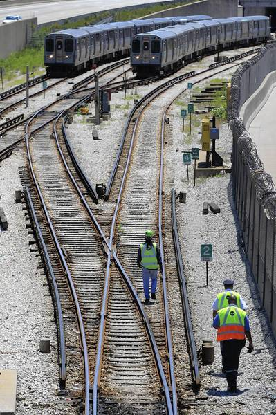 CTA workers walk the Red Line tracks just south of the 95th Street station Monday. The south branch of the Red Line, including the 95th Street station, will be closed for five months next year for repairs.