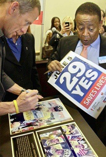 """Lance Armstrong, left, signs an autograph for Proposition 29 supporter Yesewlik """"Leo"""" Ayalew. Armstrong has donated $1.5 million to the Proposition 29 campaign."""