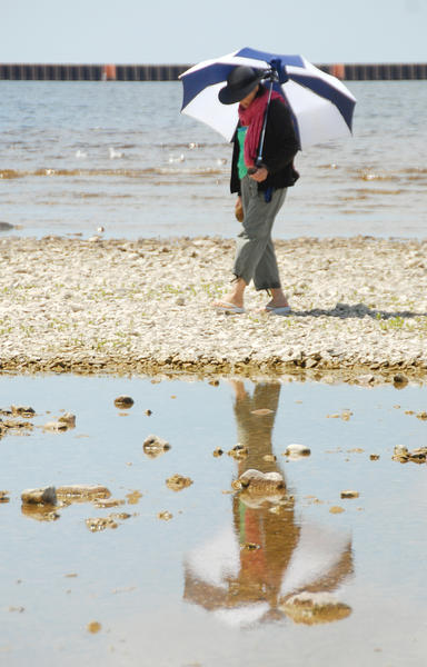Consuelo Delacruz, of Hinsdale, Ill., walks the shore of Little Traverse Bay at Petoskey, with an umbrella over her shoulder. Delacruz and her family were visiting the area for the first time and she was looking for Petoskey stones.