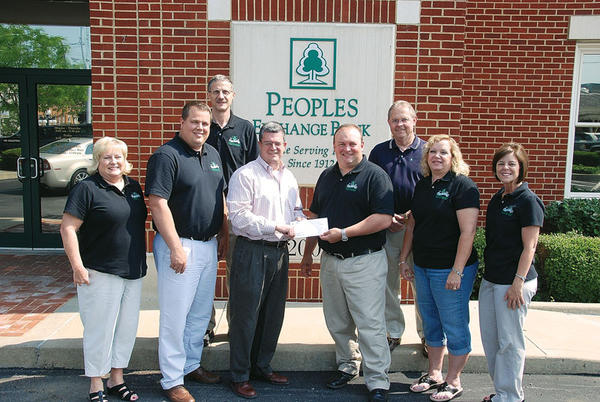 People's Exchange Bank is a sponsor of the 2012 Beer Cheese Festival. Presenting a check to Winchester First Director Tim Janes are, from left, Gloria Branham, Daniel Barry, Carl Norton, Janes, Keith Roberts, Randy Todd, Kathy Stafford and Karen Walters.