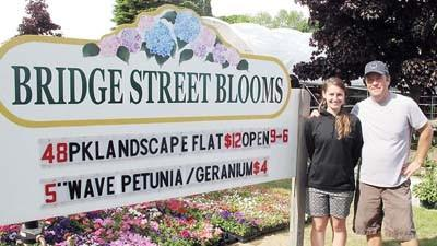 Bridge Street Blooms owner Chris Helstrom (right) stands with his daughter Kaitlyn in front of his newly-opened nursery business on Bridge Street in Charlevoix.
