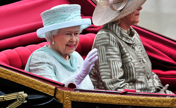 Britain's Queen Elizabeth II waves from her seat in the 1902 State Landau coach next to Camilla, Duchess of Cornwall, during the carriage procession from Westminster Hall to Buckingham Palace.