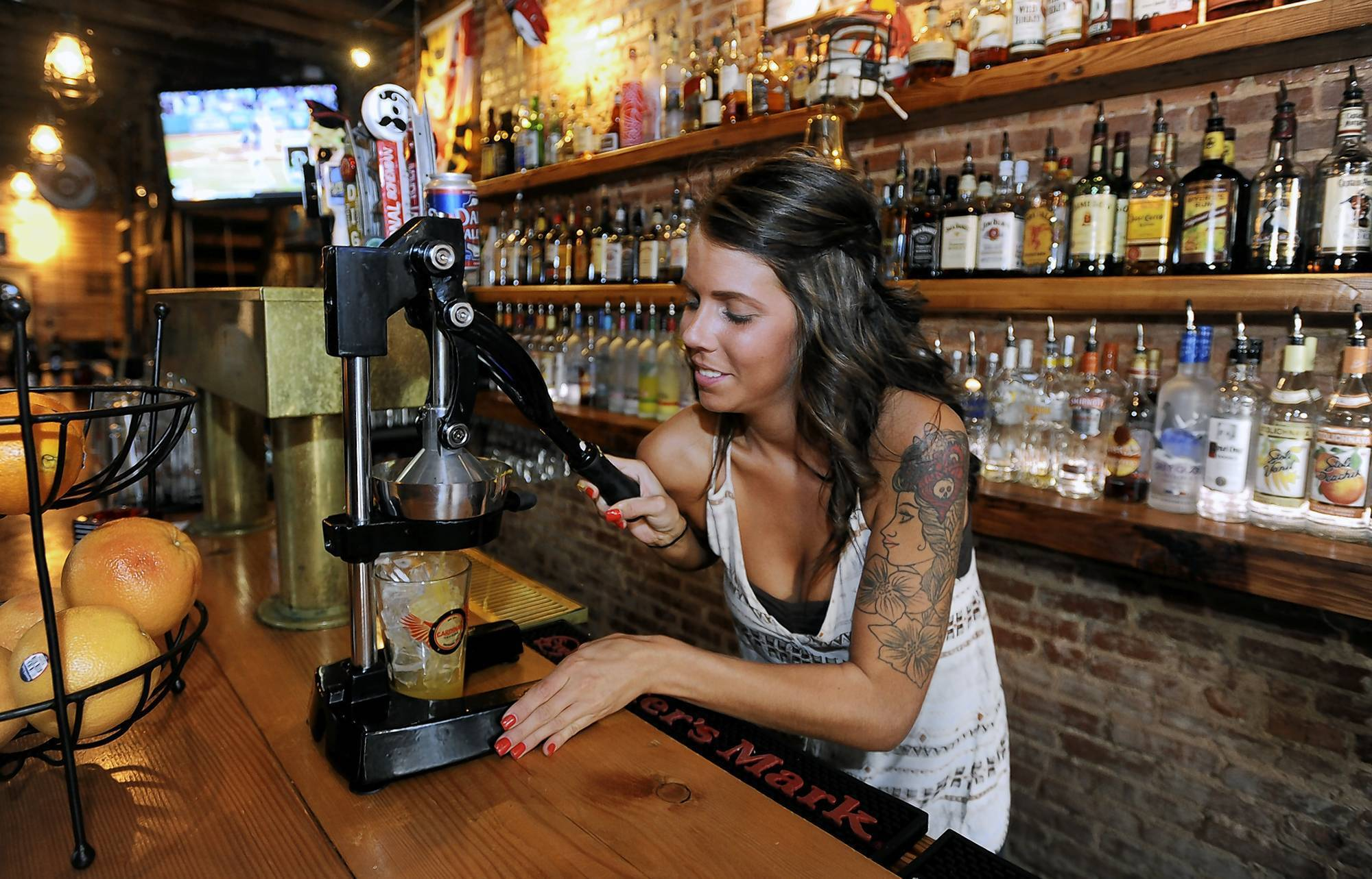 Lacey Emala, bartender at the Cardinal Tavern in Canton, makes an orange crush.