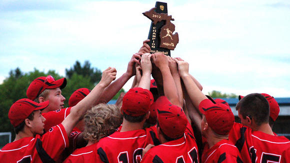 The Johannesburg-Lewiston baseball team hoists the District trophy after beating Atlanta and Hillman by a combined score of 23-2 to easily cruise Monday at St. Mary