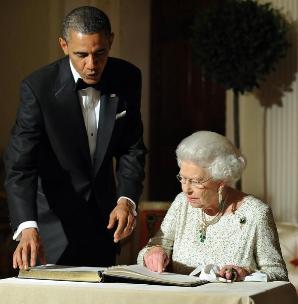 President Obama looks on as Britain's Queen Elizabeth II signs a guest book after a dinner at the Winfield House in London in May 2011.