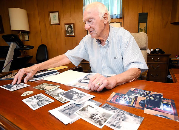 Arthur Staymates discusses the D- Day invasion while looking through photos at his Hagerstown home.