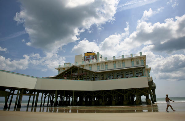 A woman walks past the newly renovated Main Street Pier in Daytona Beach on June 5, 2012. The pier reopened on Tuesday after a lenghty renovation which included a Joe's Crab Shack. There are also small vendors that sell pizza and italian ice among other things.